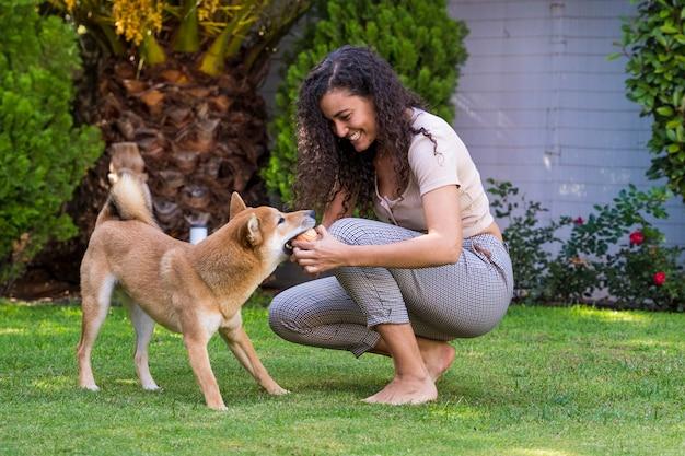 Ritratto della donna che abbraccia e che bacia il suo cane nel giardino