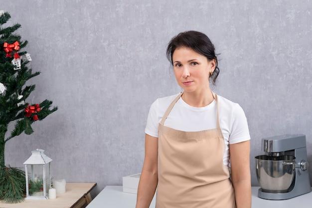 Ritratto di donna in grembiule da cucina in cucina. sfondo albero di natale.