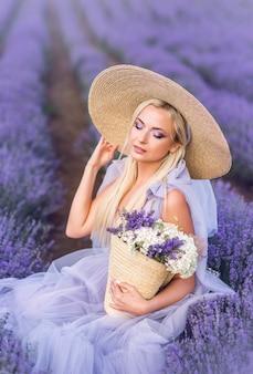 Ritratto di una donna in lavanda. una bella ragazza è seduta su uno sfondo di fiori viola. trucco occhi viola.