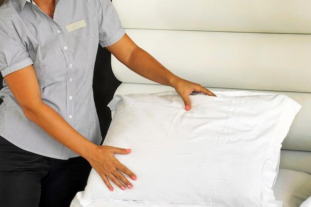Ritratto di donna cameriera che fa il letto nella camera d'albergo. governante che fa letto