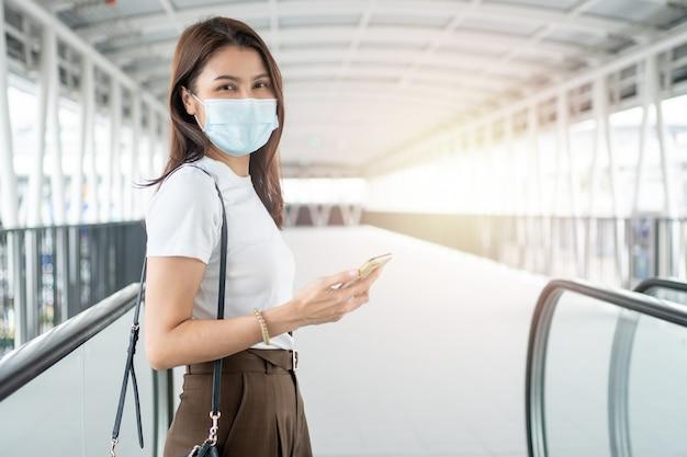Ritratto di una donna in una maschera medica utilizzando il suo smartphone all'aperto