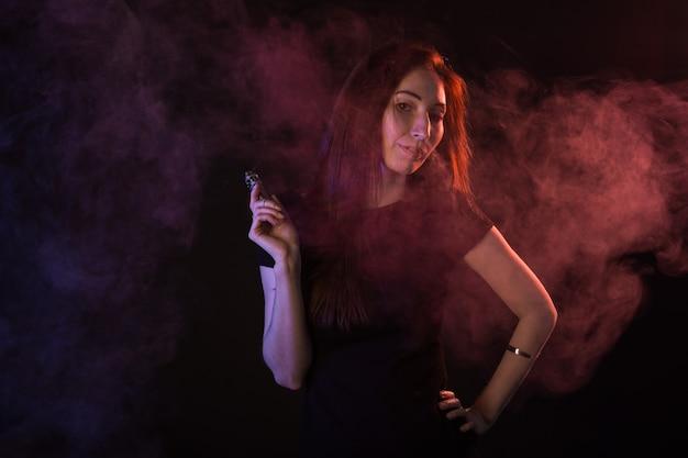 Ritratto di donna in neon fumo rosso e blu con vape o sigarette elettroniche.