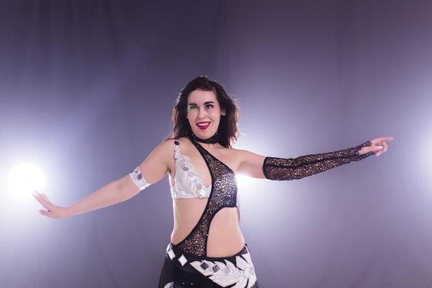 Ritratto di una donna in costume orientale che esegue la danza del ventre. concetto di danza tribale fusion.