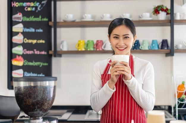 Ritratto della proprietaria di una donna in piedi al cancello della sua caffetteria con in mano una tazza di caffè