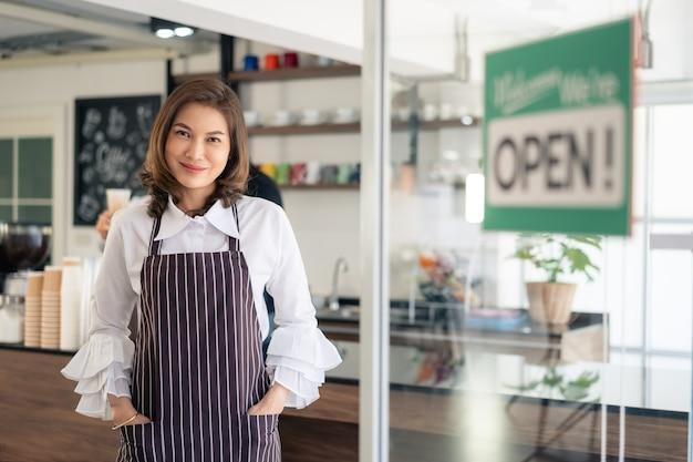 Ritratto del proprietario della donna che sta al suo cancello della caffetteria con l'insegna aperta che mostra