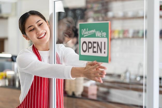 Ritratto della proprietaria di una donna in piedi al cancello della sua caffetteria con l'insegna aperta