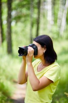 Ritratto di una fotografa che copre il viso con la fotocamera all'aperto per scattare una foto, giornata mondiale del fotografo, giovane donna con una fotocamera in mano.