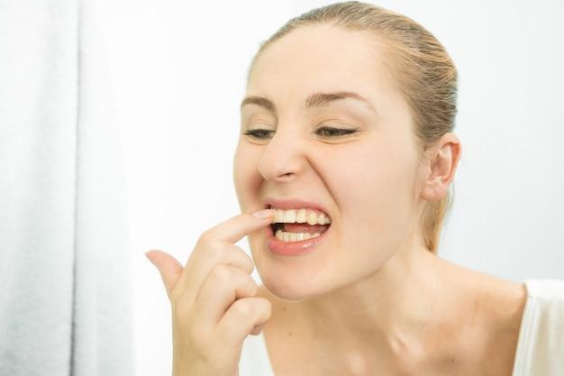Ritratto di donna che raccoglie cibo incastrato nei denti con un dito