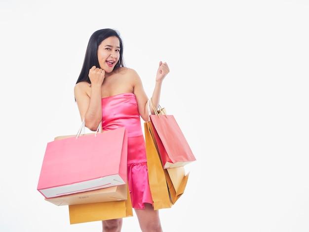 Ritratto di donna in abito rosa con borse della spesa isolato su sfondo bianco