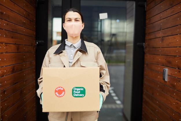 Ritratto di donna in maschera protettiva lavorando come corriere lei in piedi all'aperto e tenendo la scatola di cartone