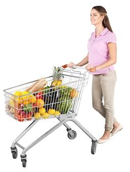 Ritratto di una donna che spinge un carrello della spesa pieno di generi alimentari