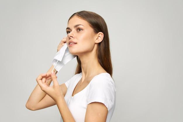 Il ritratto di una donna mette una mascherina medica sul suo fondo chiaro della maglietta bianca del fronte