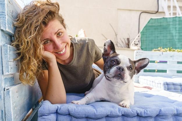Il ritratto della donna si rilassa con il bulldog a casa. vista orizzontale della donna che gioca con l'animale domestico all'aperto