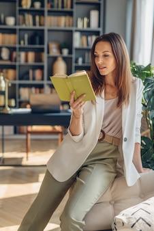 Ritratto di donna che riposa a casa e legge un libro sul divano.