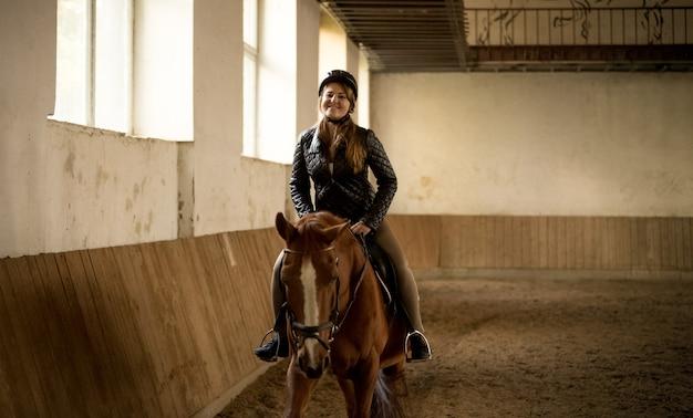 Ritratto di donna in sella a un bellissimo cavallo marrone al maneggio indoor