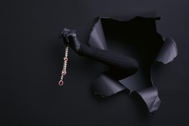 Ritratto della mano della donna in maglione nero ruba una collana di diamanti attraverso uno studio strappato
