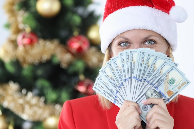 Ritratto di donna con cappello di babbo natale che tiene ventaglio con contanti dollari americani natale e nuovo