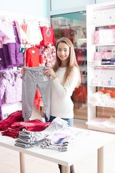 Ritratto di donna-venditrice che prepara vestiti in boutique