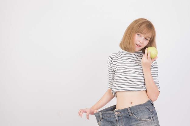Ritratto di donna mostra la perdita di peso indossando vecchi jeans, donna che tiene la frutta guava su bianco