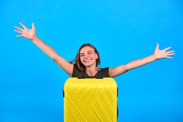 Donna ritratto sedersi con bagaglio giallo
