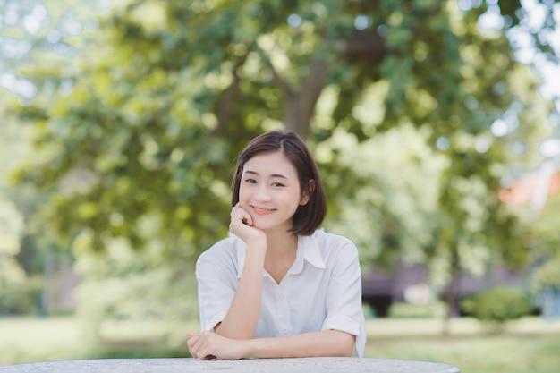 Ritratto di donna seduta su una panchina di un parco e sorridente