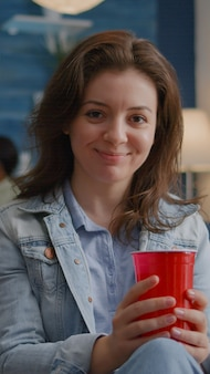 Ritratto di donna seduta sul divano similing alla fotocamera mentre beve birra a tarda notte durante le feste