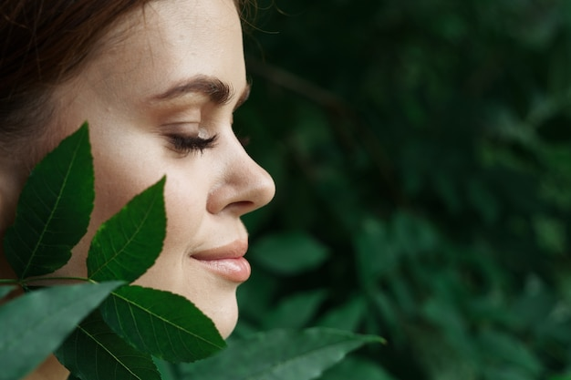 Ritratto di una donna cura della pelle spalle nude foglie verdi natura closeup