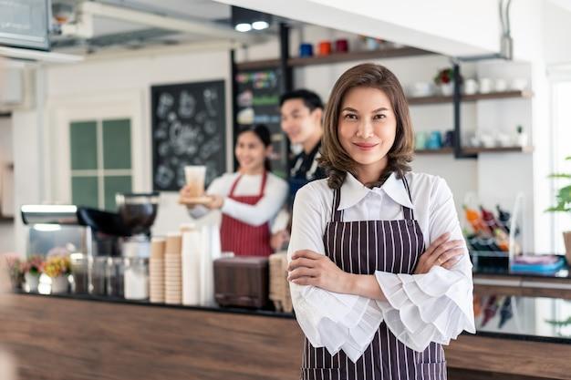 Ritratto di donna in piedi presso la sua caffetteria