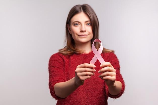 Ritratto di donna in maglione che mostra un nastro rosa, simbolo della consapevolezza del cancro al seno, guardando la telecamera