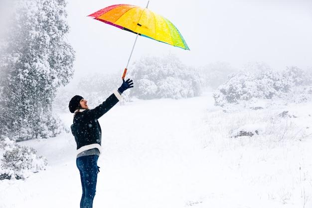 Ritratto di una donna che lancia un ombrello colorato in aria durante una nevicata.