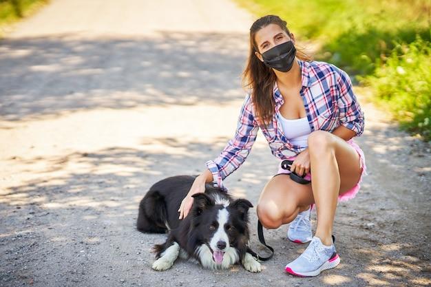 Ritratto di donna che porta a spasso un cane in campagna e indossa una maschera