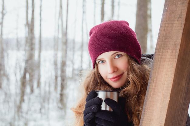 Ritratto di una donna con un cappello caldo con una tazza con una bevanda calda in mano su una natura invernale all'aperto