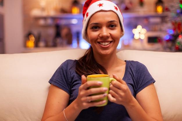 Ritratto di donna che indossa un cappello rosso da babbo natale che tiene in mano una tazza di caffè