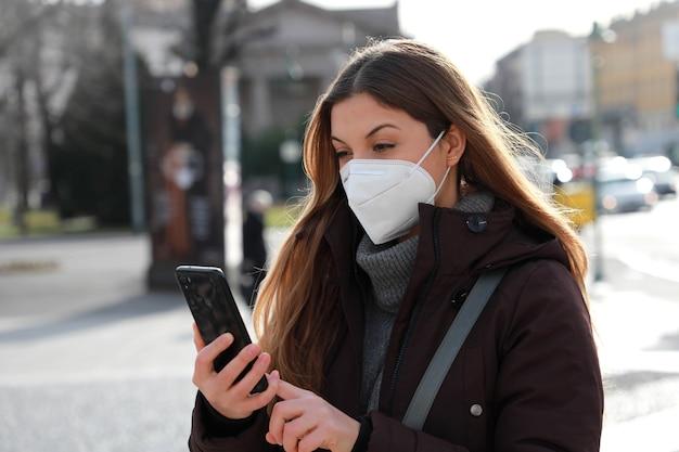Ritratto di donna che indossa giacca invernale con maschera ffp2 kn95 utilizza lo smartphone all'aperto