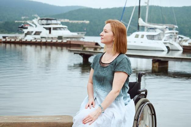 Ritratto di una donna in sedia a rotelle sullo sfondo di un molo con catamarani.