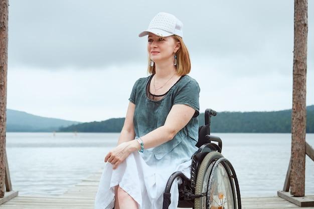 Ritratto di una donna su una sedia a rotelle con un berretto in testa, sullo sfondo di un paesaggio marino