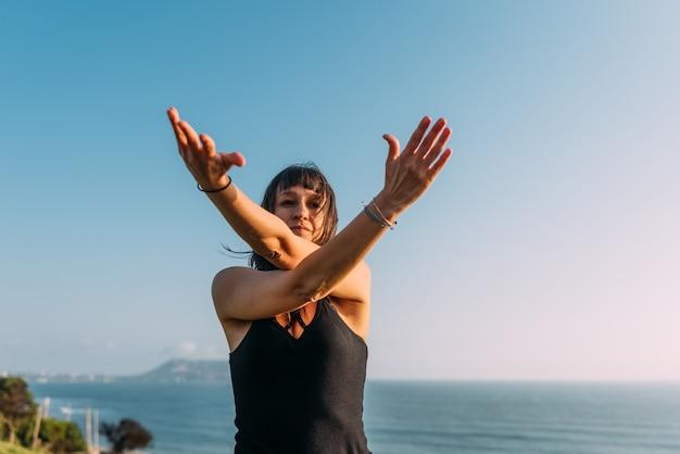 Ritratto di una donna che incrocia le braccia mentre pratica yoga e ha il cielo e il mare sullo sfondo. copia spazio
