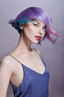 Ritratto di donna con capelli volanti dai colori vivaci, tutte le sfumature del viola. colorazione dei capelli, belle labbra e trucco. capelli svolazzanti al vento