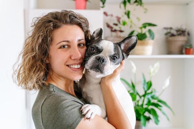 Ritratto di donna con bulldog a casa. vista orizzontale della donna che tiene il suo cane con decorazioni vegetali