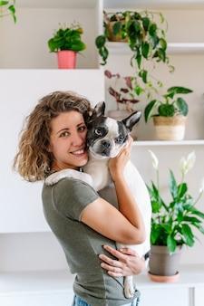 Ritratto di donna con bulldog a casa. vista verticale della donna che tiene il suo cane con decorazioni vegetali