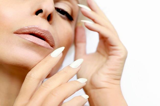 Ritratto di una donna con pelle pulita e sana e una lunga manicure con il primo piano di smalto per unghie di latte.