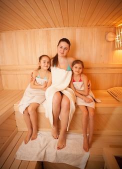 Ritratto di donna con bambine che si rilassano nella sauna finlandese