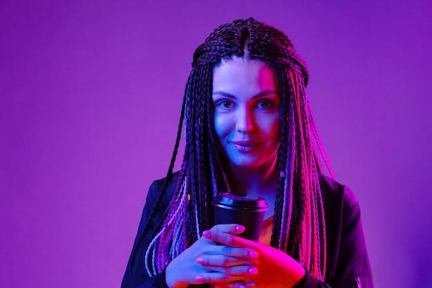 Ritratto di una donna con lunghe trecce afro che tiene una tazza di caffè su sfondo viola al neon