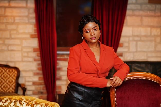Ritratto di donna con acconciatura retrò indossa giacca arancione al ristorante