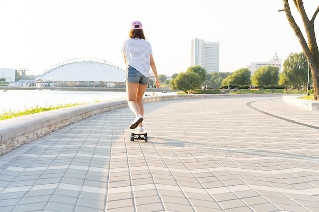 Ritratto di una donna con uno skateboard su strada, all'aperto.