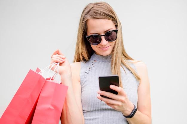 Ritratto della donna con gli occhiali da sole che passa in rassegna telefono cellulare