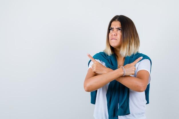 Ritratto di donna con maglione legato che punta su entrambi i lati, mordendo il labbro, alzando lo sguardo in maglietta bianca e guardando la vista frontale smemorata