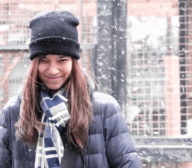 Ritratto di una donna con abbigliamento invernale con la neve
