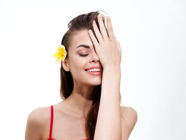 Ritratto di donna con fiore giallo tra i capelli e modello di sorriso faccia felice