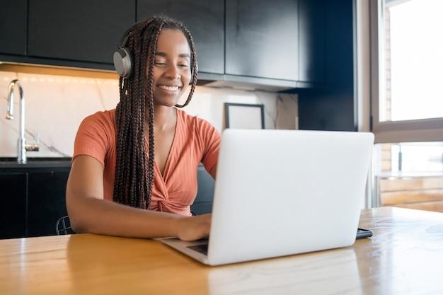 Ritratto di una donna che lavora a casa e che ha una videochiamata con il laptop.